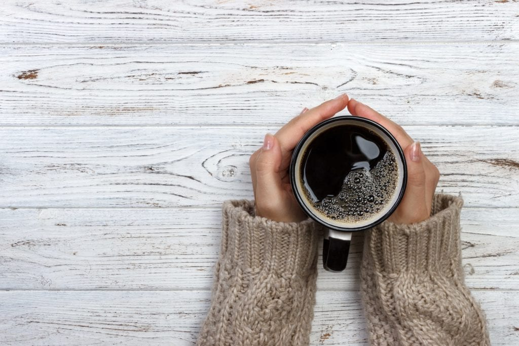 Woman hands holding coffee cup