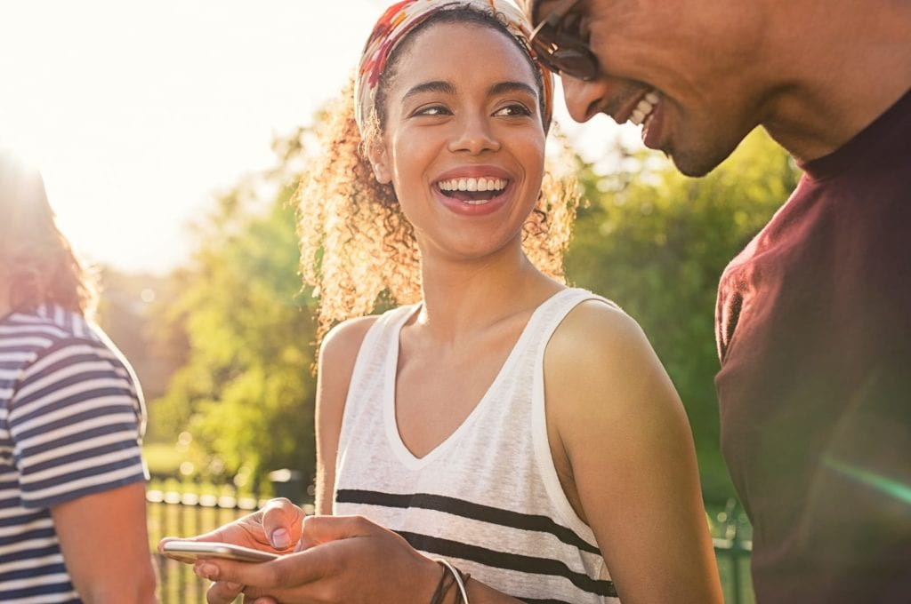 Woman laughing with man at a bar-b-que.